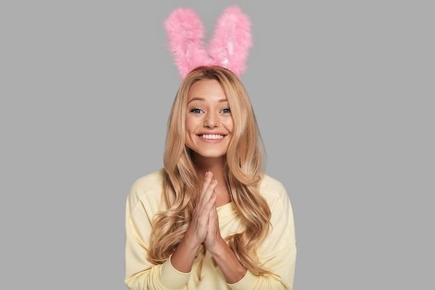 Sentindo-se excitado. mulher jovem e atraente sorridente com orelhas de coelho rosa, mantendo as mãos cruzadas e olhando para a câmera em pé contra um fundo cinza