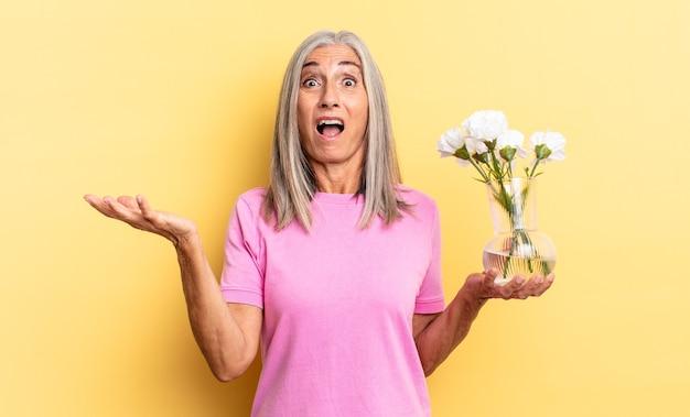 Sentindo-se extremamente chocado e surpreso, ansioso e em pânico, com um olhar estressado e horrorizado segurando flores decorativas
