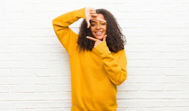 Sentindo-se feliz, amigável e positivo, sorrindo e fazendo um retrato ou moldura com as mãos