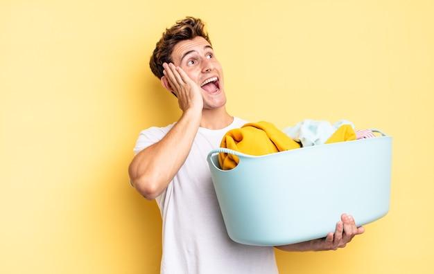 Sentindo-se feliz, animado e surpreso, olhando para o lado com as duas mãos no rosto. conceito de lavagem de roupas
