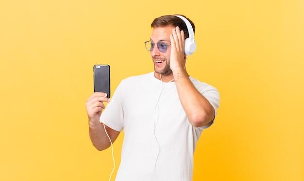 Sentindo-se feliz, animado e surpreso, ouvindo música com fones de ouvido e um smartphone