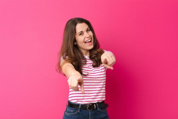 Sentindo-se feliz e confiante, apontando com as duas mãos e rindo, escolhendo você