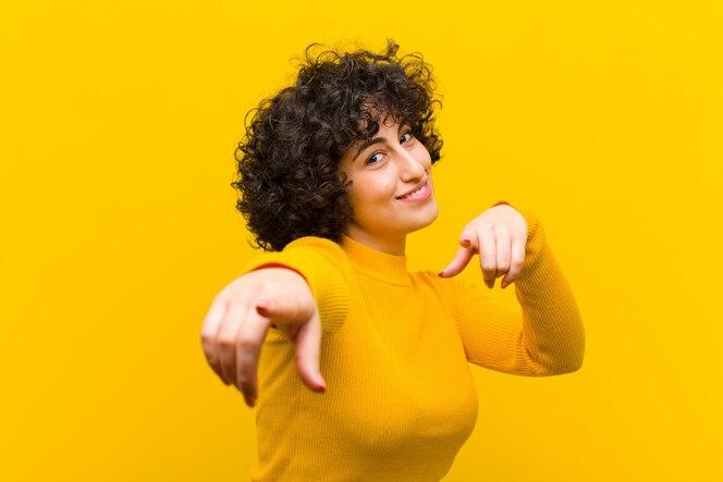 Sentindo-se feliz e confiante, apontando para a câmera com as duas mãos e rindo, escolhendo você