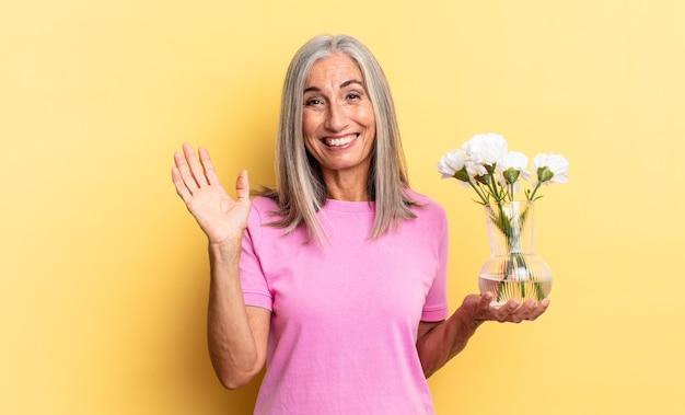 Sentindo-se feliz, surpreso e alegre, sorrindo com atitude positiva, percebendo uma solução ou ideia segurando flores decorativas