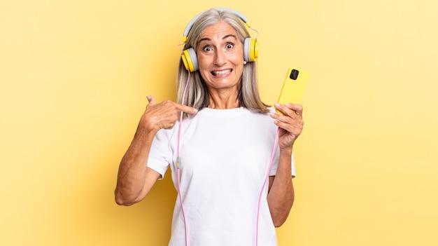 Sentindo-se feliz, surpreso e orgulhoso, apontando para si mesmo com um olhar animado e surpreso com fones de ouvido