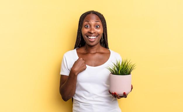 Sentindo-se feliz, surpreso e orgulhoso, apontando para si mesmo com um olhar animado e surpreso segurando um vaso de plantas