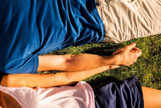 Sentindo-se felizes juntos. vista superior de um casal apaixonado, de mãos dadas enquanto estava deitado na grama verde