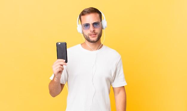 Sentindo-se intrigado e confuso, ouvindo música com fones de ouvido e um smartphone