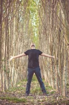 Sentindo-se livre, despreocupado e livre levantando os braços rodeado da natureza, curtindo a vida