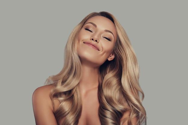Sentindo-se livre e relaxado. mulher jovem e bonita de olhos fechados e sorrindo em pé contra um fundo cinza