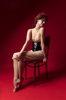 Sentindo-se perfeita. jovem ruiva medieval como uma duquesa em espartilho preto e roupa de noite, sentada na cadeira na parede vermelha. conceito de comparação de eras, modernidade e renascimento.