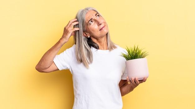Sentindo-se perplexo e confuso, coçando a cabeça e olhando para o lado segurando uma planta decorativa