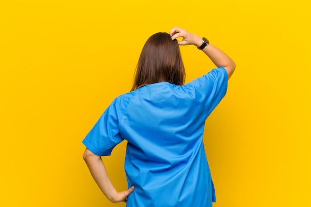 Sentindo-se sem noção e confuso, pensando em uma solução, com a mão no quadril e outro na cabeça, vista traseira isolada contra parede amarela
