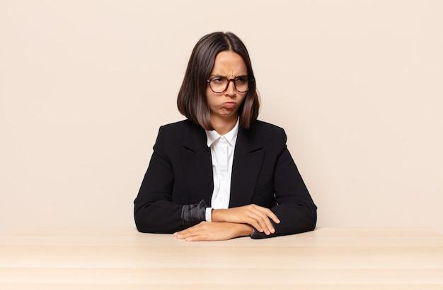 Sentindo-se triste, chateado ou com raiva e olhando para o lado com uma atitude negativa, franzindo a testa em desacordo