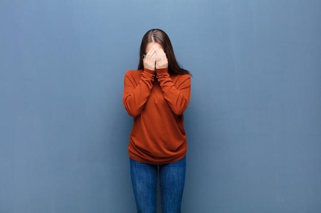 Sentindo-se triste, frustrado, nervoso e deprimido, cobrindo o rosto com as duas mãos, chorando