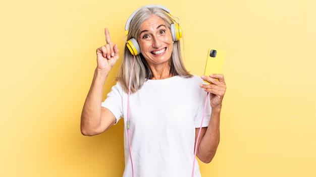 Sentindo-se um gênio feliz e animado depois de realizar uma ideia, levantando o dedo alegremente, eureka! com fones de ouvido