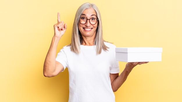 Sentindo-se um gênio feliz e animado depois de realizar uma ideia, levantando o dedo alegremente, eureka! e segurando uma caixa branca