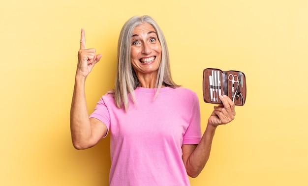 Sentindo-se um gênio feliz e animado depois de realizar uma ideia, levantando o dedo alegremente, eureka! segurando um estojo de ferramentas de pregos