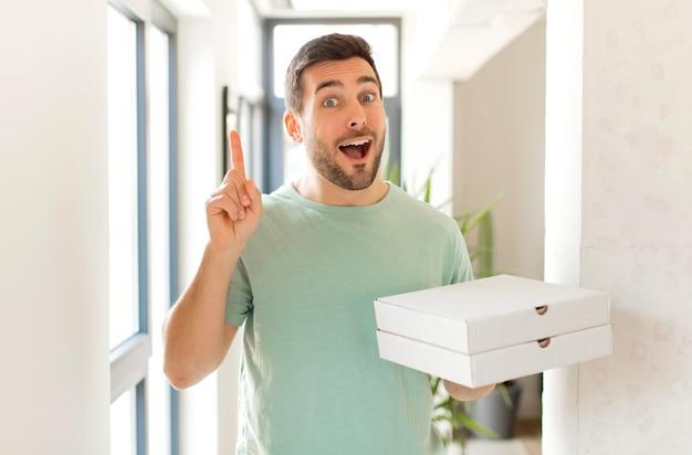 Sentindo-se um gênio feliz e animado depois de realizar uma ideia, levantando o dedo alegremente, eureka!