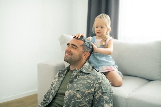 Sentindo-se verdadeiramente aliviado. oficial militar sentindo-se verdadeiramente aliviado ao voltar para casa após o serviço e brincar com a filha