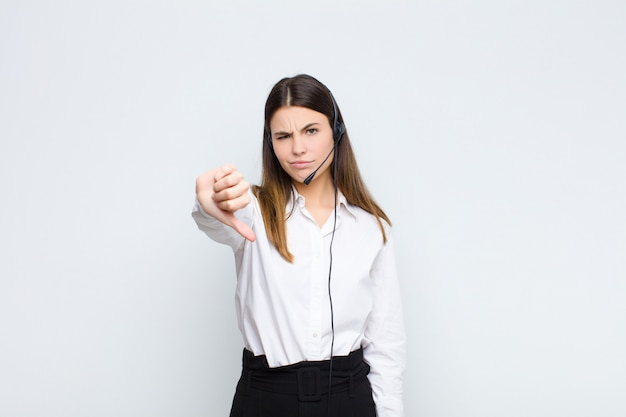 Sentindo-se zangado, irritado, desapontado ou descontente, mostrando os polegares para baixo com um olhar sério
