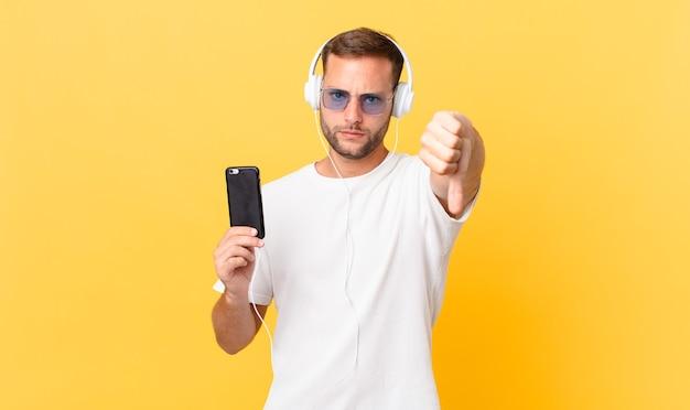 Sentindo-se zangado, mostrando os polegares para baixo, ouvindo música com fones de ouvido e um smartphone