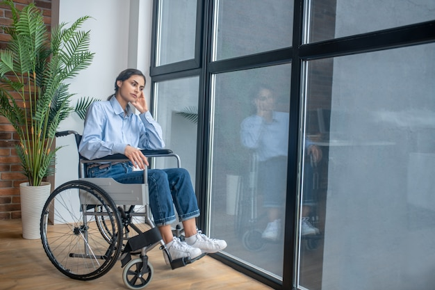 Sentindo solitário. uma jovem em uma cadeira de rodas parecendo frustrada e chateada