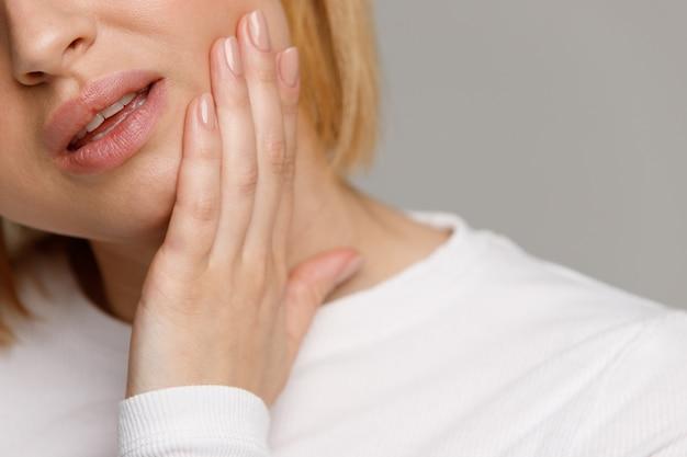 Sentir dor feminina, segurando sua bochecha com a mão, sofrendo de dor de dente ruim