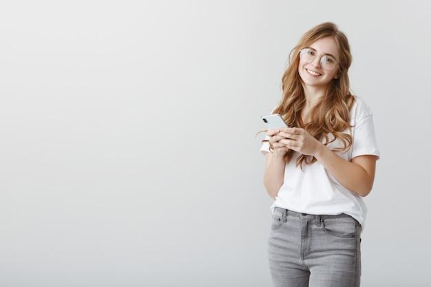 Sentir-se bem no círculo de amigos. aluna europeia feliz comum de óculos e roupas casuais, segurando um smartphone, meio virada de pé e sorrindo amigavelmente, recebendo palavras calorosas