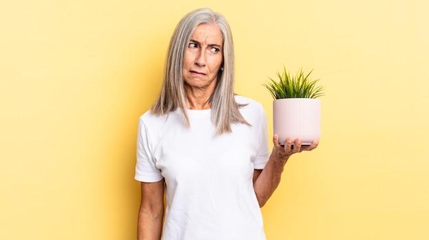 Sentir-se triste, chateado ou com raiva e olhando para o lado com uma atitude negativa, franzindo a testa em desacordo segurando uma planta decorativa