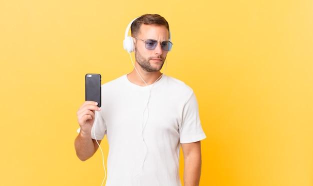 Sentir-se triste, chateado ou com raiva e olhando para o lado, ouvindo música com fones de ouvido e um smartphone
