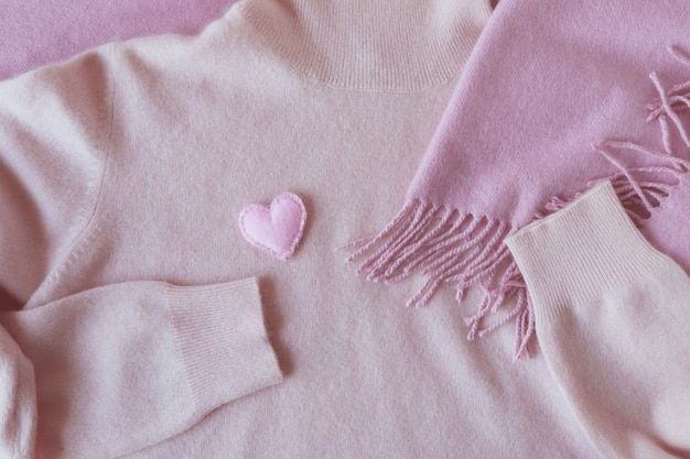 Sentiu corações em roupas de caxemira rosa, vista superior, conceito de dia dos namorados, produtos aconchegantes e aconchegantes