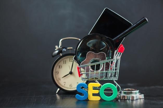 Seo search engine optimization letras coloridas de seo com relógio, lupa, smartphone, engrenagens em uma cesta.