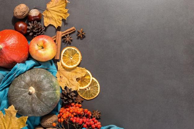 Seque as folhas amarelas, maçãs, nozes, abóboras, especiarias, castanhas e cones na mesa. humor de outono, copyspace, plana leigos.