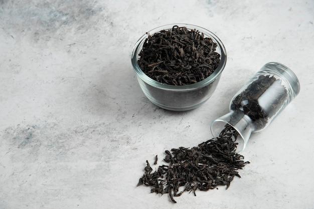 Seque as folhas de chá em uma tigela de vidro no mármore.