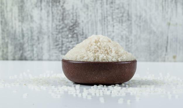 Seque em volta do arroz em uma bacia no branco e no fundo do grunge. vista lateral.