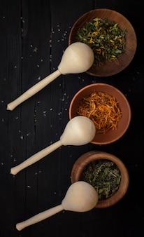 Seque ervas medicinais em diferentes recipientes com colheres de madeira em um fundo preto de madeira