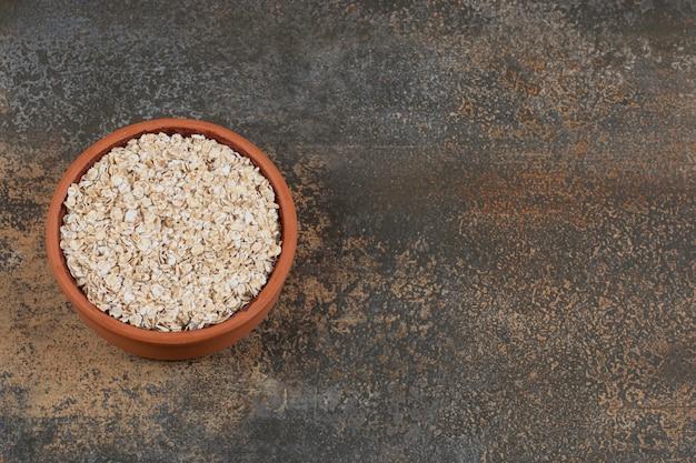 Seque flocos de aveia em uma tigela de cerâmica.