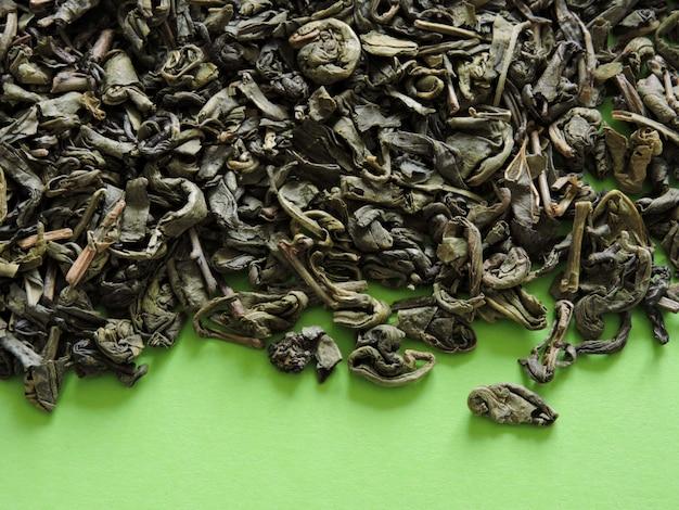 Seque o chá verde sobre um fundo verde claro. vista do topo. copie o espaço.