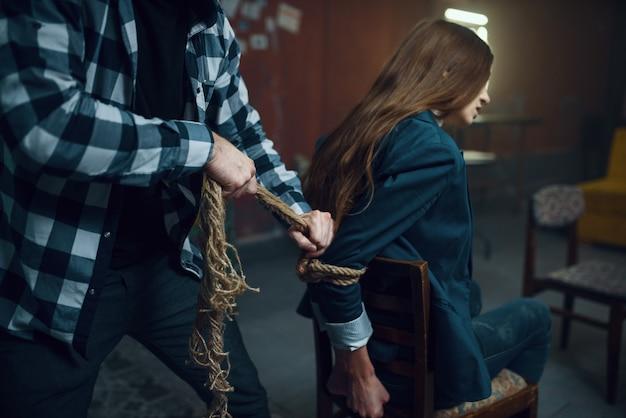 Seqüestrador maníaco amarra sua vítima feminina com uma corda. seqüestro é um crime grave, louco psicopata, terror de sequestro, violência