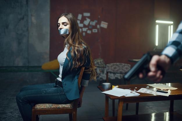 Seqüestrador maníaco com uma arma, vítima feminina com medo no fundo. seqüestro é um crime grave, louco psicopata, terror de sequestro, violência