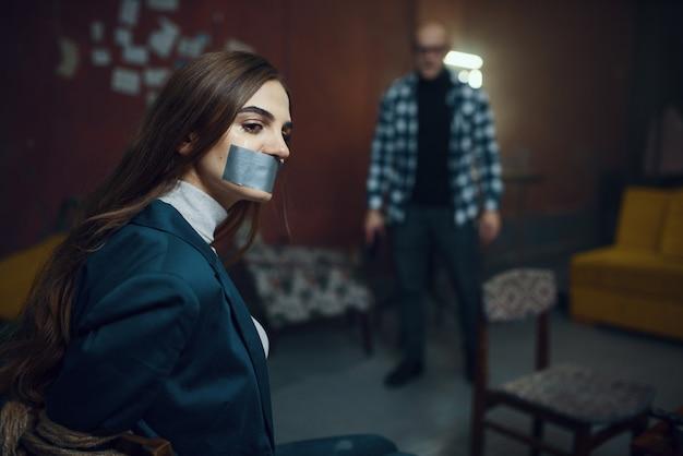 Seqüestrador maníaco e vítima feminina com a boca fechada com fita adesiva. seqüestro é um crime grave, louco psicopata, terror de sequestro, violência