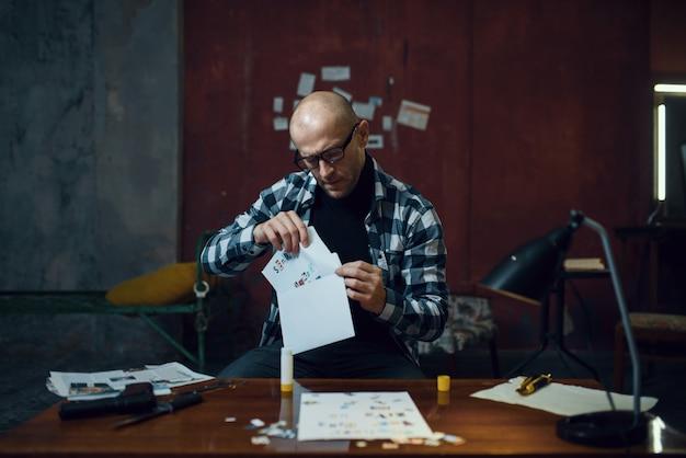 Seqüestrador maníaco prepara carta sobre sua vítima. seqüestro é um crime grave, psicopata do sexo masculino em seu apartamento
