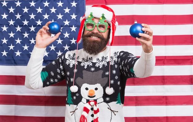 Ser americano pode ser divertido. homem barbudo se divertir no ano novo. papai noel patriótico no banner star spangled. decoração festiva. diversão de véspera de natal. boas festas. felicidades do feriado. saudações de temporadas. a diversão começa.
