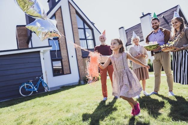 Ser ativo. garota gentil segurando balões enquanto corre com prazer