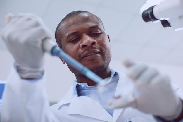 Ser biólogo. cientista habilidoso e inspirado conduzindo um exame de sangue e vestindo um uniforme