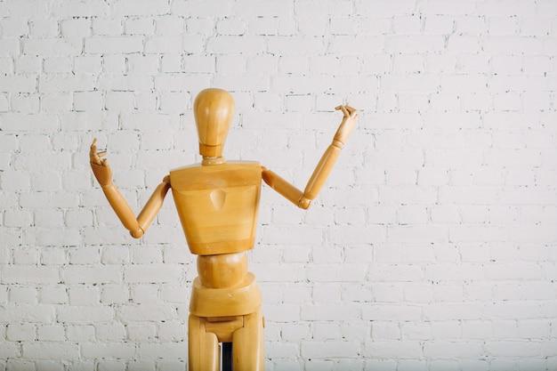Ser humano de madeira na parede de tijolo branco com espaço da cópia