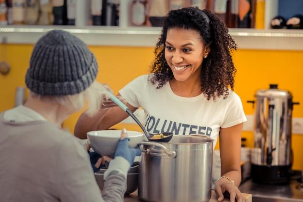 Ser voluntário. mulher simpática e simpática sorrindo enquanto desfruta de seu trabalho como voluntária