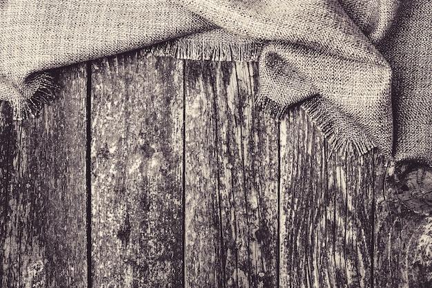 Serapilheira em fundo de madeira. pano de cozinha na mesa de madeira rústica, vista superior. têxteis de toalha de mesa no pano de fundo. cozinhar comida ou pizza na mesa de madeira com têxteis. copie o espaço para o texto
