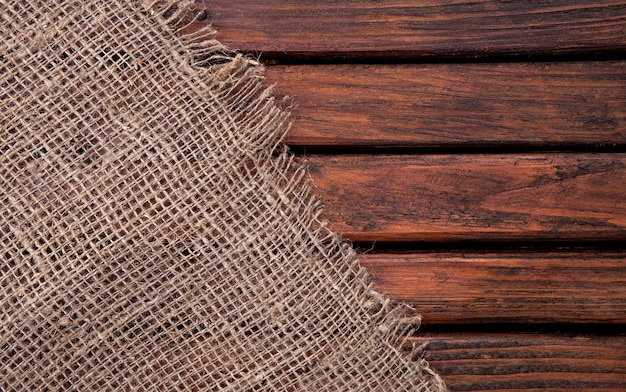 Serapilheira hessian demissão no fundo escuro de madeira